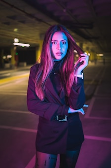 Young brunette caucasian girl at night in an underground parking lot, illuminated with neon lights