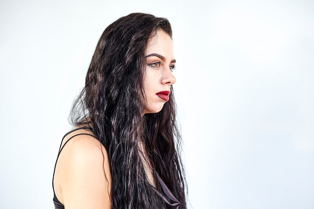 Young brunette caucasian girl in profile on a white background