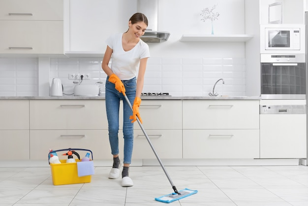 Молодая брюнетка убирает пол на кухне