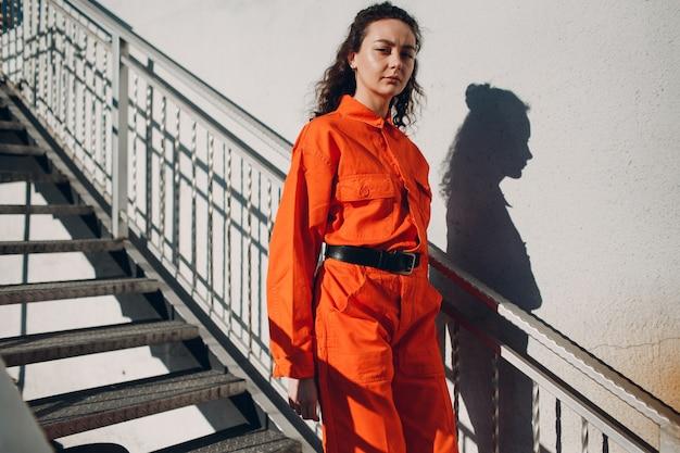 オレンジ色のスーツを着た若いブルネットの巻き毛の女性。カラフルなオーバーオールの肖像画の女性。