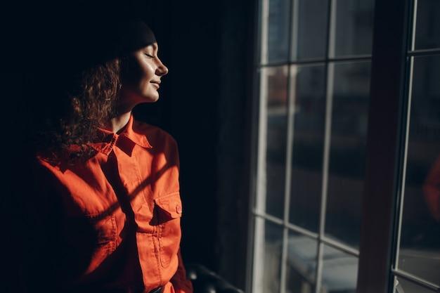 Молодая брюнетка фигурная женщина в оранжевом костюме. женщина в портрете красочных комбинезонов.