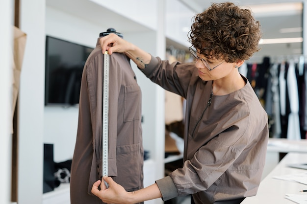 Young brunette curly woman measuring sleeve length of jacket on mannequin while working in her studio