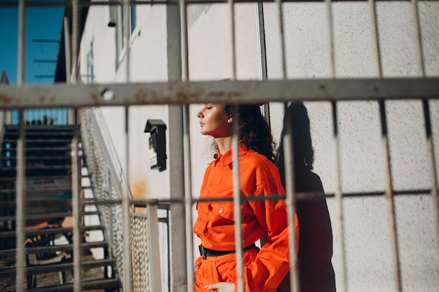 Young brunette curly woman in orange suit behind cage. female in colorful overalls portrait.