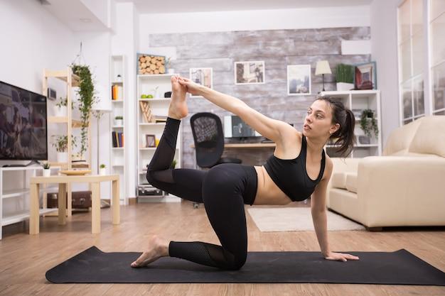 Giovane bruna che fa esercizio per l'equilibrio sulla stuoia di yoga in casa.