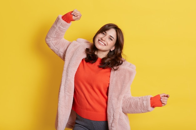 Молодая брюнетка возбужденная европейская девушка в теплом меховом пальто, двигающая руками под звуки музыки, с зубастой улыбкой, выражающая счастье, стоит изолированно на желтой стене