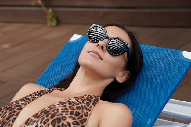 Young brunette female in black sunglasses lies on blue deck chair and sunbathing, beautiful girl wearing swimming suit with leopard print relaxing at resort.