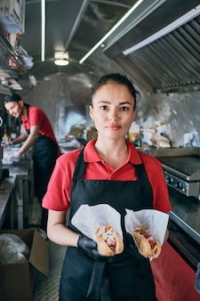 2つのホットドッグを保持しているファーストフードの若いブルネットの女性店員