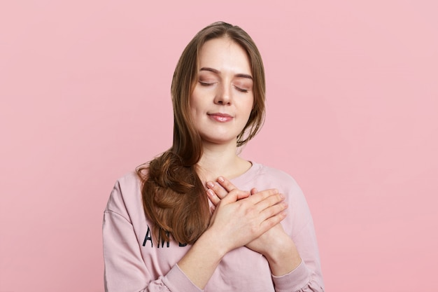 Young brunette female has friendy look, keeps hands on chest, closes eyes, being satisfied with calm domestic atmopshere, isolated over pink studio wall. friendly relaxed woman