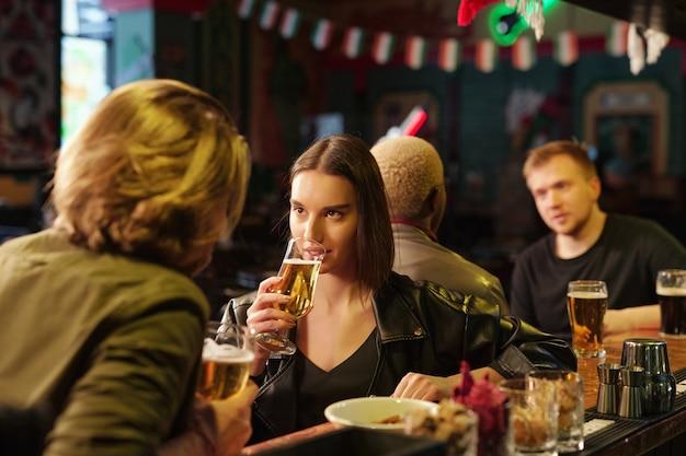 黒革のジャケットとプルオーバーでビールを飲み、2人の男とバーカウンターでチャット中に彼女のボーイフレンドを見ている若いブルネットの女性