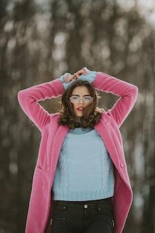안경을 쓴 젊은 갈색 머리 여성과 추운 겨울 날에 포즈를 취하는 분홍색 재킷