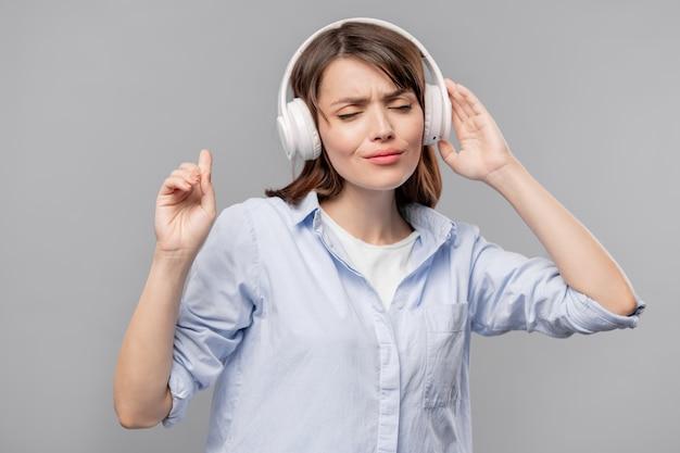 Молодая брюнетка женщина в наушниках, наслаждаясь своей любимой музыкой, позирует в изоляции