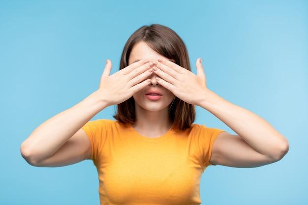 立っている間手で彼女の目を覆っている黄色のtシャツの若いブルネットの女性