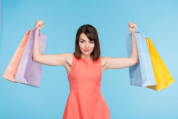 Young brunette female shopper lifting paperbags after successful shopping in the mall or trade center