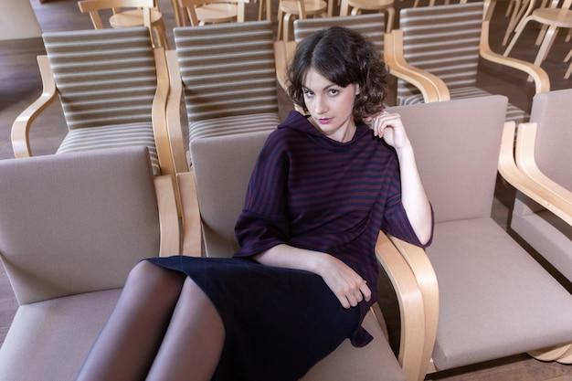 Lyceumに一人で座っている若いブルネットの女子学生。