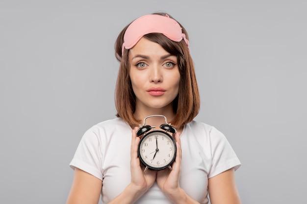 Молодая брюнетка женщина с будильником, показывая 7 утра стоя