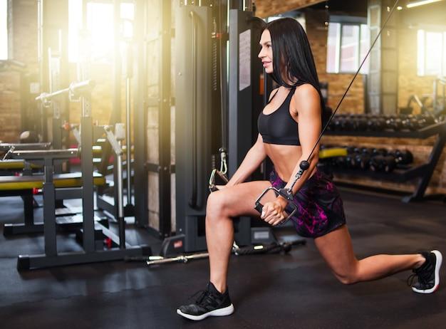 Женщина молодой брюнет подходящая выполняет тренировку с кроссовером кабеля тренажера в спортзале. процесс тренировки