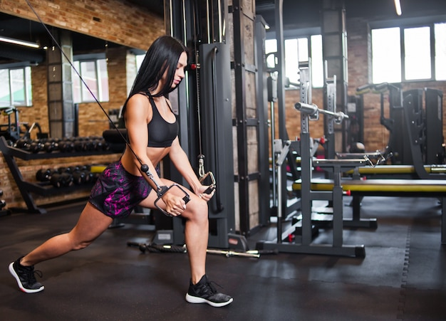 Young brunette fit woman execute exercise with exercise machine in gym