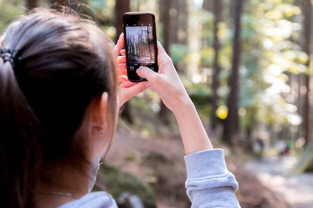 A young brunette in a forest takes a photo on their smartphone