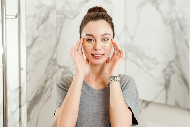 Young brunette girl in bathroom applying eye patches with a smile