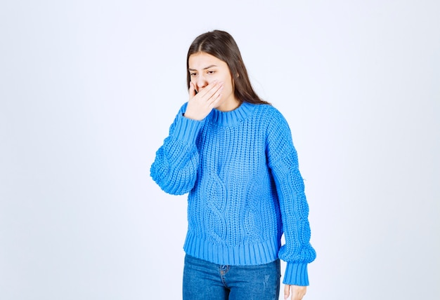 Young brunette girl in blue sweater wants to throw up on white.kk