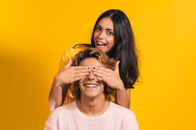 黄色の背景で若いブロンドの男の子に目を覆って、遊んでいる若いブルネットの少女