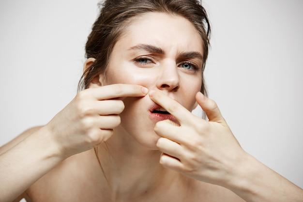 白い背景の上の彼女の問題にきび顔肌に不満の若いブルネットの少女。健康美容とスキンケア。