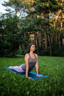 A young brunette girl does yoga in nature. bhujangasana