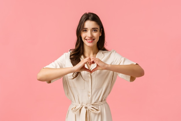 Young brunette girl in dress, showing heart sign