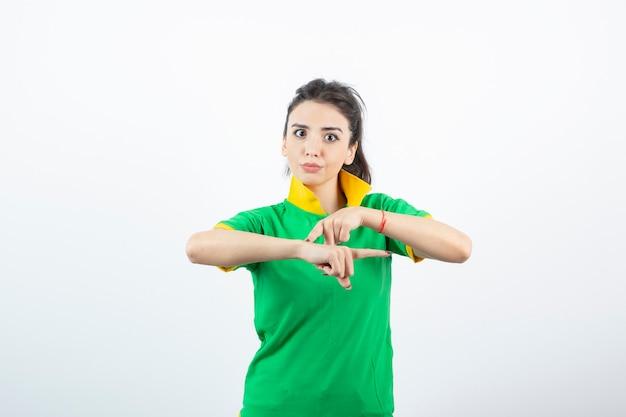 Giovane ragazza bruna in maglietta verde in piedi e alla ricerca.