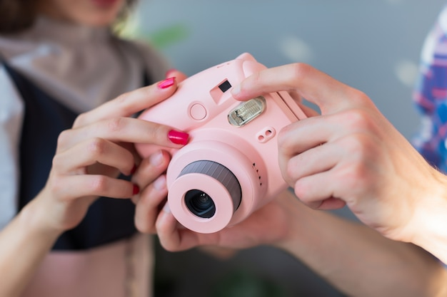 A young brunette girl and a guy look at photo taken on an instant camera