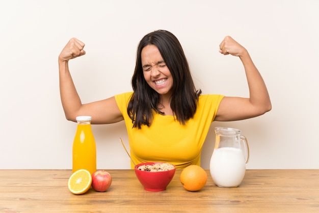 Young brunette girl having breakfast milk celebrating a victory