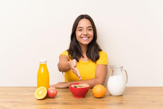 Young brunette girl having breakfast milk handshaking after good deal