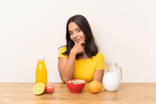 Young brunette girl having breakfast milk laughing