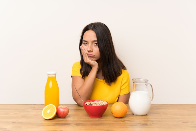 Young brunette girl having breakfast milk unhappy and frustrated