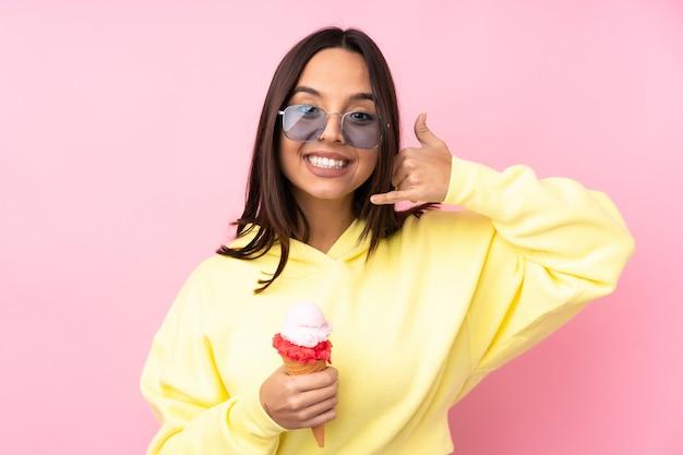 電話のジェスチャーを作る孤立したピンクの背景の上にコルネットアイスクリームを保持している若いブルネットの少女。コールバックサイン