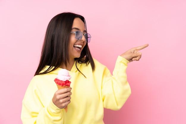 横に指を指し、製品を提示する孤立したピンクの背景の上にコルネットアイスクリームを保持している若いブルネットの少女