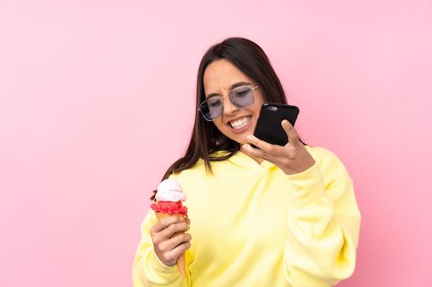 勝利の位置に電話で孤立したピンクの背景の上にコルネットアイスクリームを保持している若いブルネットの少女
