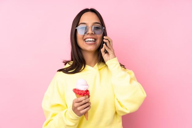 携帯電話との会話を維持している孤立したピンクの上にコルネットアイスクリームを保持している若いブルネットの少女