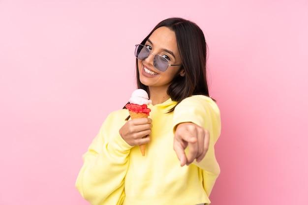 孤立したピンクの上にコルネットアイスクリームを保持している若いブルネットの少女は、電話のジェスチャーをして正面を指しています