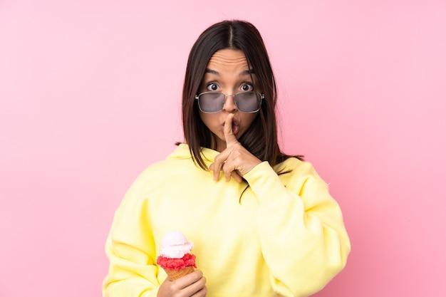 Молодая брюнетка девушка держит мороженое корнет над изолированным розовым, показывая знак жестом молчания, кладя палец в рот