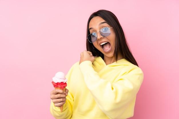 Молодая брюнетка девушка держит мороженое корнет над изолированной розовой стеной, празднуя победу