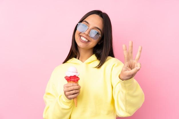幸せな孤立したピンクの壁の上にコルネットアイスクリームを保持し、指で3を数える若いブルネットの少女