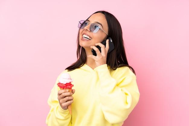 持ち帰り用のコーヒーと携帯電話を保持している孤立したピンクの壁の上にコルネットアイスクリームを保持している若いブルネットの少女