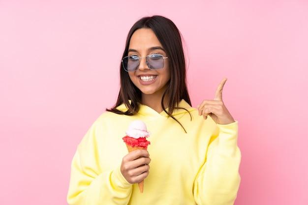 素晴らしいアイデアを指している孤立したピンクの壁にコルネットアイスクリームを保持している若いブルネットの少女