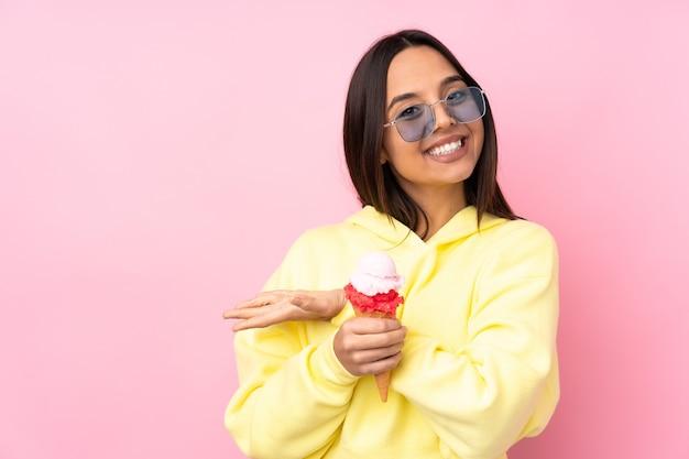 に向かって笑顔を見ながらアイデアを提示する孤立したピンクの壁にコルネットアイスクリームを保持している若いブルネットの少女