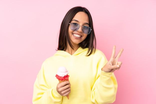 고립 된 분홍색 벽에 코 넷 아이스크림을 들고 웃 고 승리 기호를 보여주는 젊은 갈색 머리 소녀