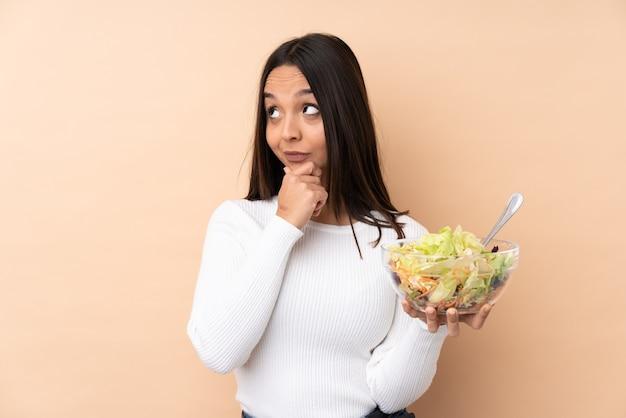 Молодая брюнетка девушка держит салат на изолированном фоне, сомневаясь и с смущенным выражением лица