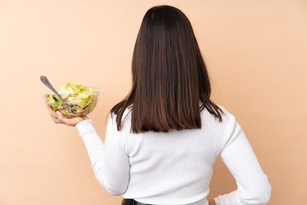 Молодая брюнетка девушка держит салат на изолированном фоне в заднем положении