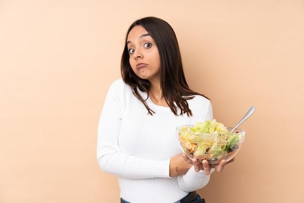 Молодая брюнетка девушка держит салат на изолированном фоне, делая жест сомнения, поднимая плечи