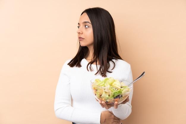 Молодая брюнетка девушка держит салат на изолированном фоне портрета